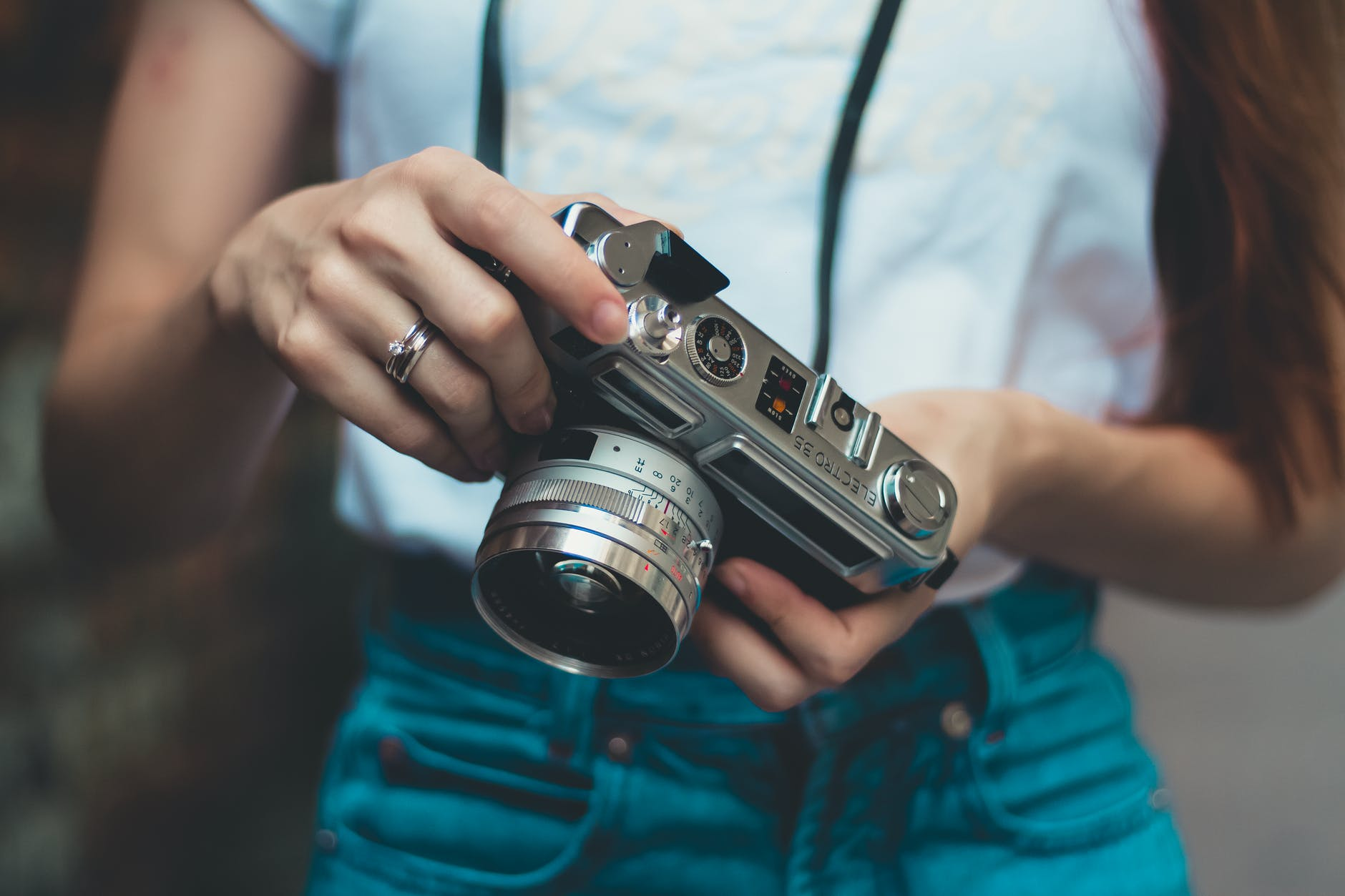 woman in white shirt holding analog camera