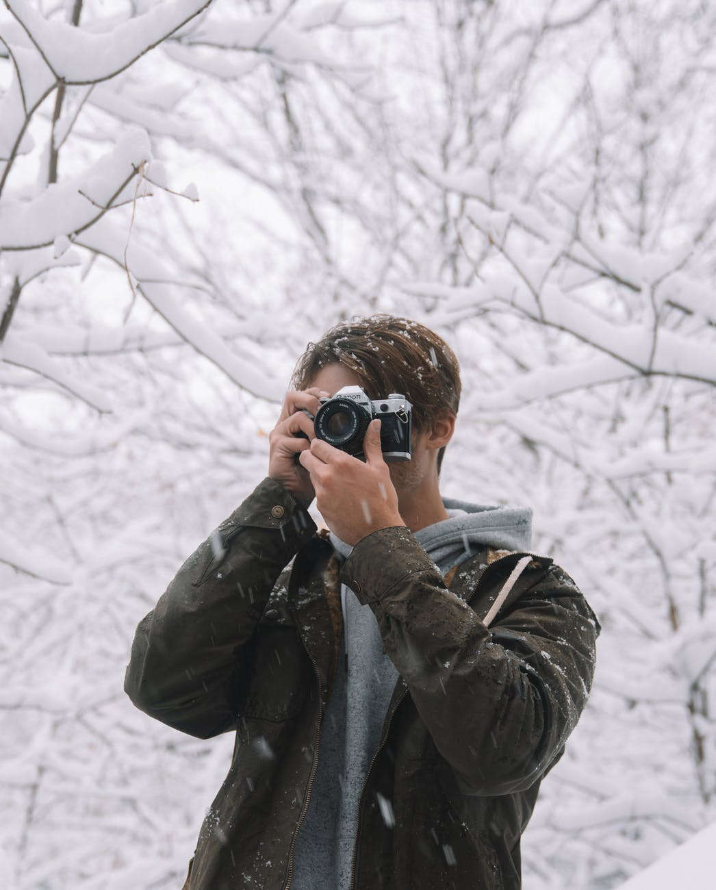 male photographer taking photo in winter woods