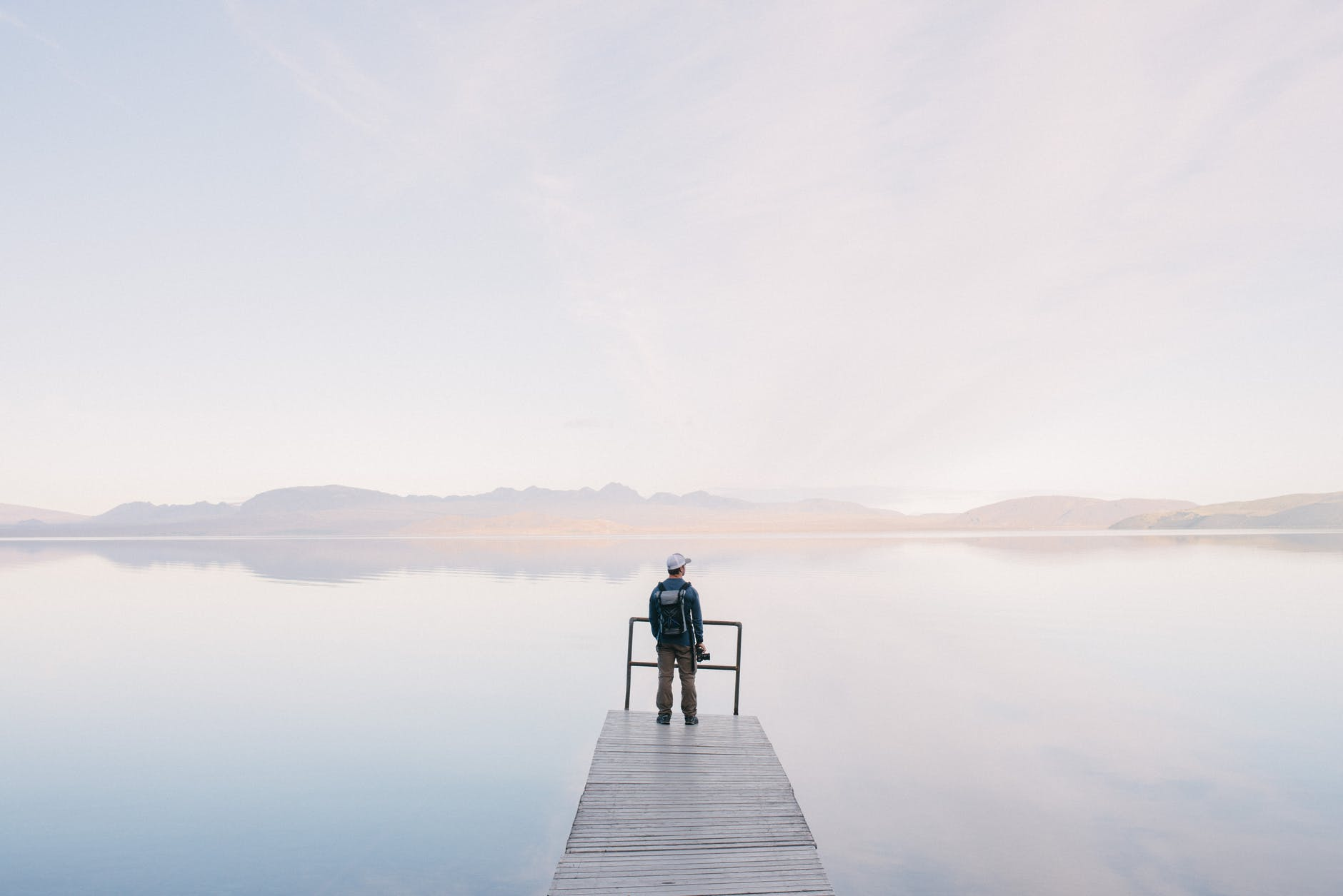 man wearing jacket standing on wooden docks leading to body of water