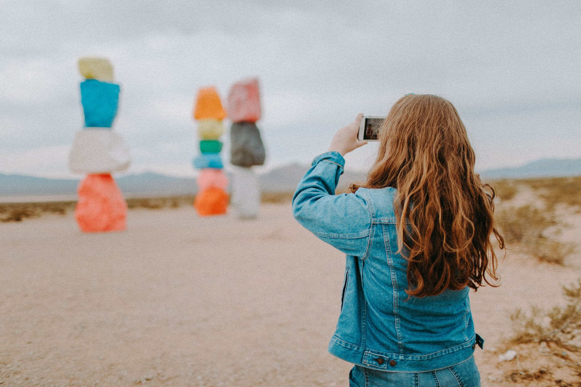 woman in blue denim jacket taking photos